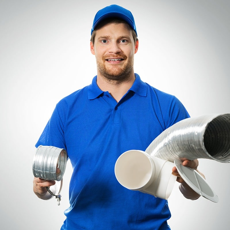 A technician holding ductwork pipes