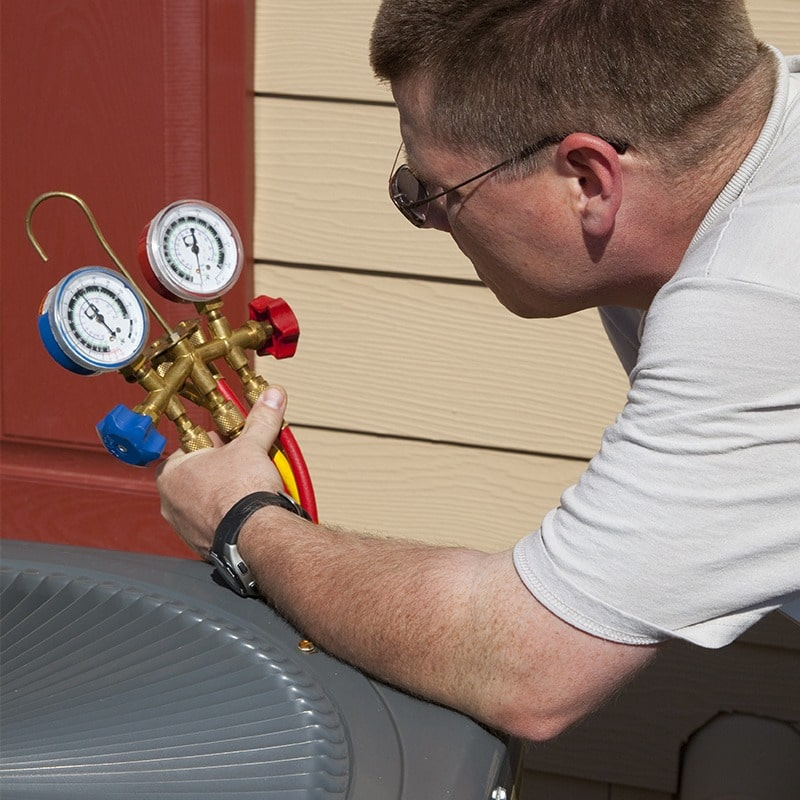 A techniciian measuring the unit's refrigerant charge