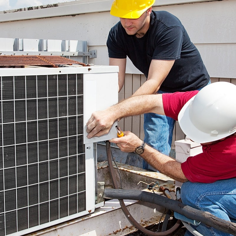 Two technicians repairing the outdoor unit
